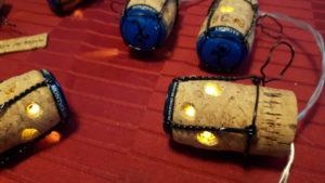 Détail - Guirlande lumineuse de couleur jaune en bouchons en liège avec des capsules bleutées, utilisée en chemin de table pour une table jolie et une ambiance chaleureuse ou pour décorer